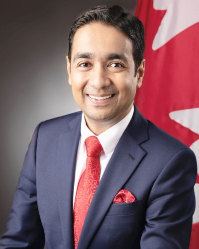 an image of a southeast asian man sitting in front of the canadian flag